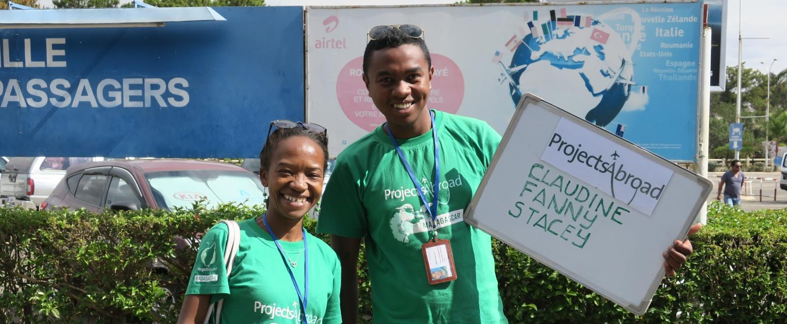 Staff stand and wait for the volunteers with the Projects Abroad sign in Madagascar.
